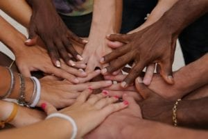 A diversity of hands rest on top of each other to show support and empowerment.