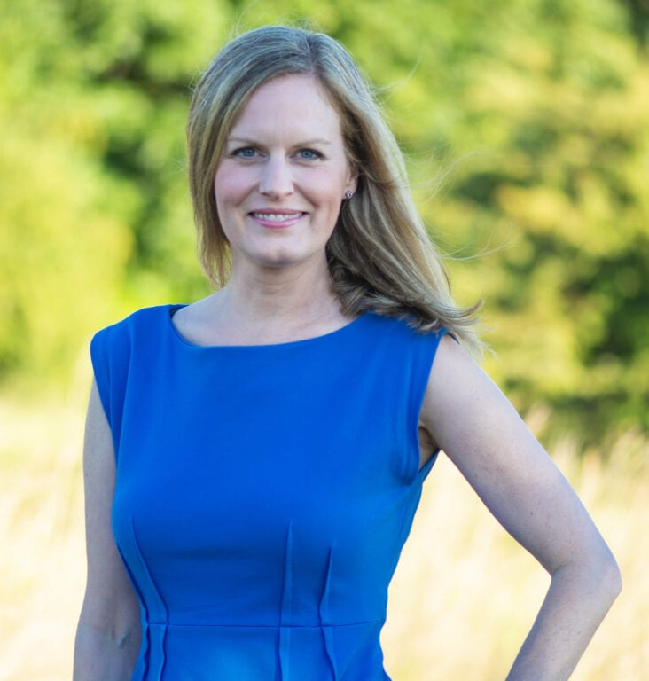 Jennifer Whitaker smiling, wearing a blue dress, and standing near the trees and water