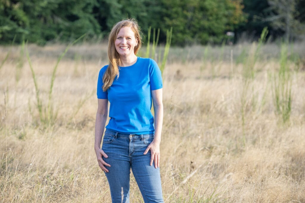 Jennifer smiling and wearing a blue shirt and jeans while standing in a grassy field