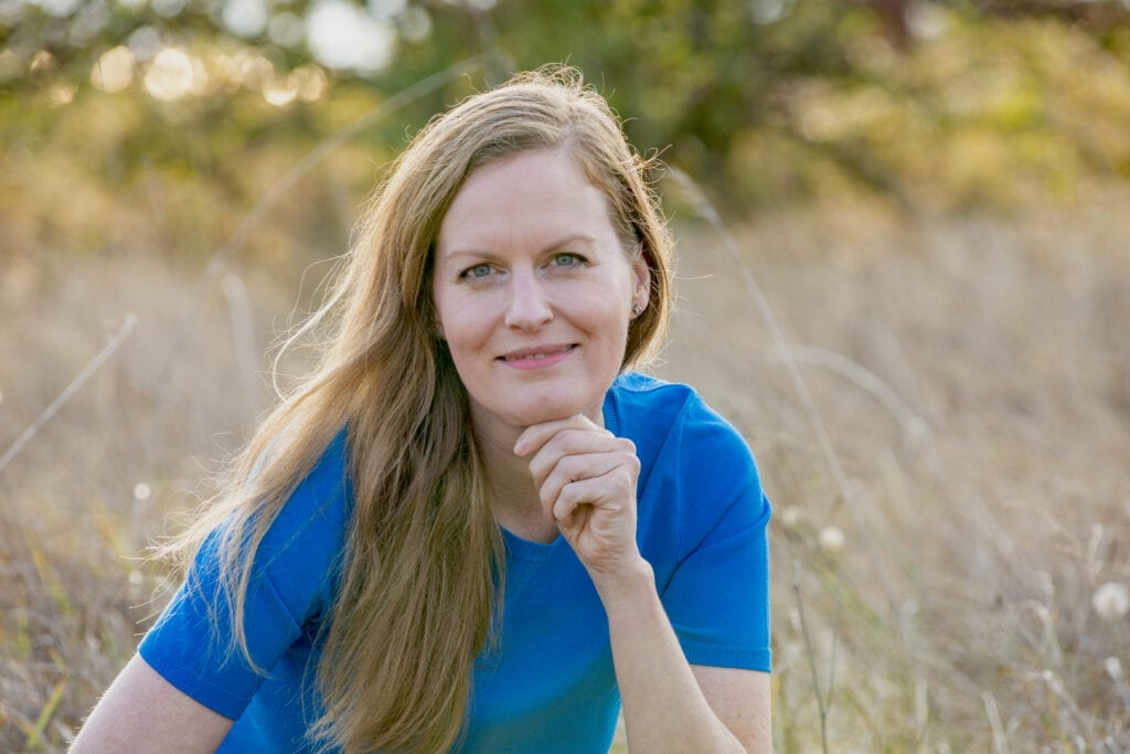 Jennifer smiling and wearing a blue shirt and jeans while sitting in a grassy field
