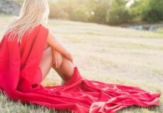Blonde woman sitting in the grass wearing a red cape