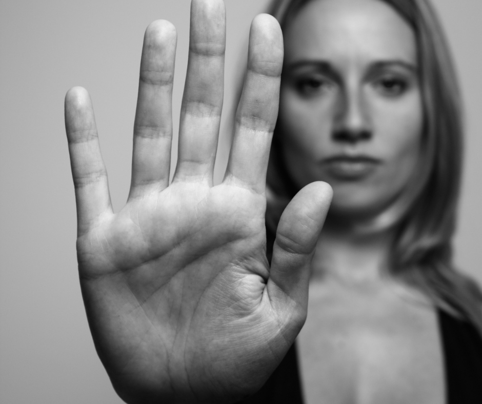 Black and white photo of woman holding up her palm in the stop position